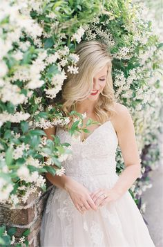 Bride with wall of jasmine flowers. Charleston SC wedding inspiration on film, featuring a Monique Lhuillier wedding gown. Photographed by Michael and Carina Photography