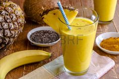 smoothie: Close up fresh blended fruit smoothies made with pineapple, banana, coconut, turmeric and chia seeds surrounded by raw ingredients in drinking glass with pineapple slice garnish and blue striped straw