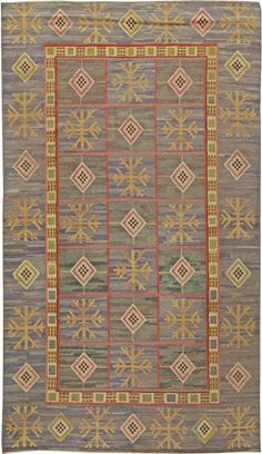 An early 20th century pile rug by famed designer Marta Maas Fjetterstrom. Traditional geometric Scandinavian design in green, red, yellow and brown.