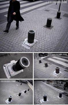 車をよけけるために設置されたポールを、カメラの望遠レンズのように見せた広告