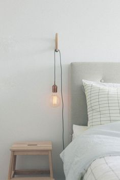 Simple bedroom and nighstand vignette with single bulb pendant string light, gray tufted headboard, gray and white graph checked pillow case, and blonde wood nightstand.