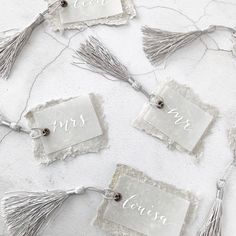 Luxury wedding place setting tags with hand written white calligraphy on vellum, handmade grey paper, an antique copper eyelet and a grey tassel for a wedding in Provence