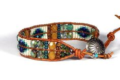 Loom Bracelet amber blue turquoise leaf Seed Bead Leather Wrap Bracelet This is a loom bracelet made with 11/0 seed beads on naturally dyed golden brown leather from the USA. The colors are amber and browns with cream, blue turquoise and green. The button is silver metal concho style.