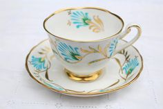 Surround yourself with lifes little luxuries. Our cup features distinct turquoise and gold gilt design on a crisp white bone china background. The saucer mirrors the same pretty pattern. She pings beautifully. Royal Chelsea fine bone china was produced from 1943-1966 All photos are