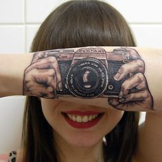 (Photo of Lotte van den Acker, from Brunssum, Holland and the vintage 1970s Asahi Pentax 35mm SLR tatooed onto her forearm by Helma van der Weide — the tattoo artist and Lotte's mother) — Rex Features via The Telegraph (vía lustik)