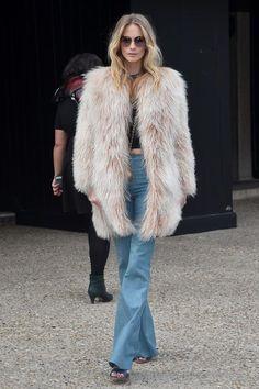 """Einen Look müssen wir noch aus der großen Paris Fashion Week-Schatzkiste hervorkramen, weil er genau das beschreibt, was uns diese Saison erwartet: Poppy Delevingne zeigt auf der Miu Miu Show eindrücklich, dass die 70er mit lautem Knall zurück sind. In Schlaghosen des Labels, dem riesigen rosa Fellmantel, bauchfreiem Top, großer Sonnenbrille und welliger Frisur könnte Poppy auch in der Fortsetzung zu """"Almost Famous"""" mitspielen."""