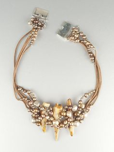 Fossilized walrus tusk woven with champagne and copper freshwater pearls on natural leather cord.        16″ long