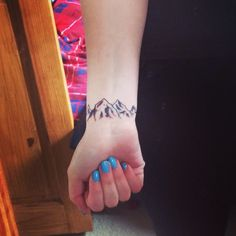 My first tattoo- little mountains on my wrist to represent skiing
