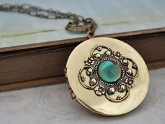 Beautiful vintage 70s brass locket decorated with detailed Victorian style stamping and with rare 2 tone vintage 50s blue and green glass cab sets in