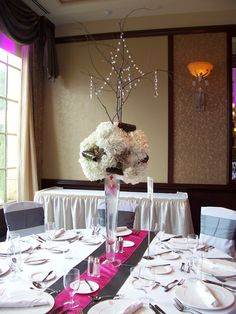 A tall centerpiece with white hydrangea, pink cymbidium orchids, with branching and crystals.