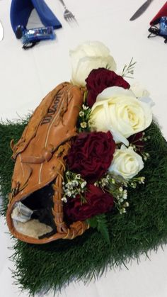 A baseball Mitt holding red Hearts roses, white chocolate roses and white wax flowers on astroturf. Baseball Wedding Centerpieces, Sports Centerpieces, Wedding Table Themes, Flower Centerpieces, Wedding Reception, Wedding Ideas, Desi Wedding, Centerpiece Ideas, Wedding Trends
