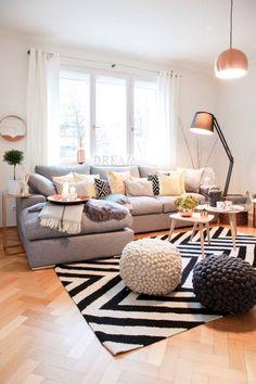 Soggiorno scandinavo con le pareti bianche, pavimento in legno chiaro e arredamento in una combinazione bianco, nero e grigio con alcuni tocchi di colore giallo - Start Preventivi
