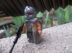 This post-apoc minifigure comes to life with the RT Helmet!  And the he looks especially deadly carrying those guns!  I know I wouldn't want to be at the other end of those weapons.  I also really like the custom trench coat that the minifig is wearing! #lego #minifigure #brickwarriors #helmet #guns #weapons #postapoc #apocolego