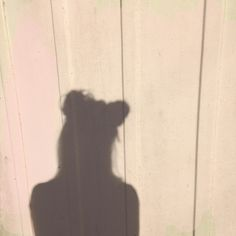 a silhouette of a person against a background of wooden planks
