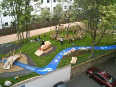 "In addition to the climbing structure, the blue ""stream"" provides drainage, preventing rainwater from pooling up in the playground."