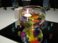 Colorful silk petals in water with a floating candle - perfect for a rainbow wedding!