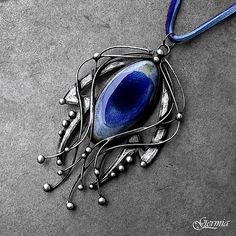 """""""Waterfall"""" by Germia. Beautiful ceramic cabochon with blue glassy surface   (hand-made) forms the center of jewelry design in the shape of an abstract falling water. Jewelry is finely decorated in several ways-engraved, polished, decorated with balls of tin and bonding, patinated, polished, signed and treated with an antioxidant."""