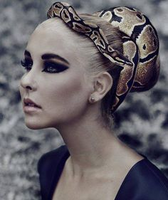 This image shows a girl with one snake wrapped around her head. This pulls from the traditional idea of Medusa and gives it a unique spin. The dark makeup and stoic look emit an evil aura.