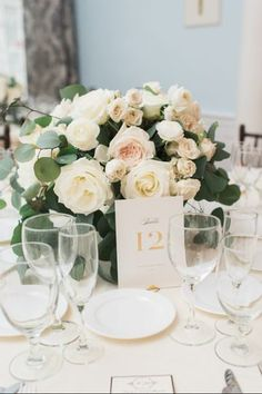 Classic table centerpiece with white roses and greenery. Find your florist at WeddingWire!