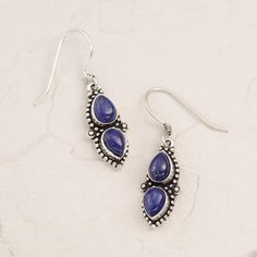 Rich and regal semi-precious lapis stones dangle from an etched silver setting, making this unique pair a perfect addition to any look.
