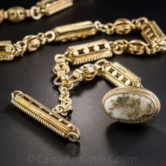They don't come any cooler than this treasure from the days of the '49ers (the originals - circa 1849). Wearable as a choker necklace at just over 15 inches, this elaborately designed Victorian watch chain, fabricated in rich 14K rosy-yellow gold, culminates in a half-football-shaped fob (consistent with the 49ers theme!) inlaid with glistening golden quartz and accented on top with worn black enamel tracery. A matching T-bar that can easily be added to increase the length of the necklace.