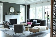 Stylish gray and black contemporary living room is furnished with a stunning curved black velvet tufted sofa placed on a gray rug in front of a wall of windows dressed in charcoal gray pleated curtains layered over white roman shades.
