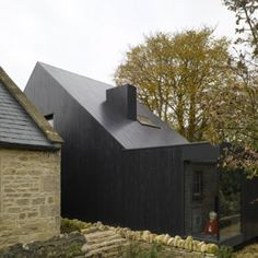 Shadow House by Jonathan Tuckey Design This house is covered with bitumen stained larch as a way of disguising it and ensuring the Chapel is not overshadowed by a new and different extension. Beautiful.