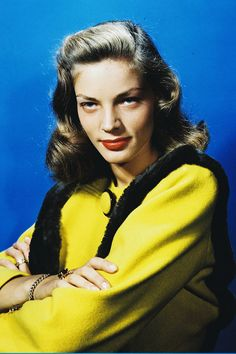 Lauren Bacall wearing a yellow jacket with black trim in a studio portrait, circa 1945
