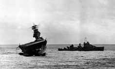 The USS Yorktown lists heavily to port after being struck by Japanese bombers and torpedo planes in the Battle of Midway on June 4, 1942. A destroyer stands by at right to assist as a salvage crew on the flight deck tries to right the stricken aircraft carrier.