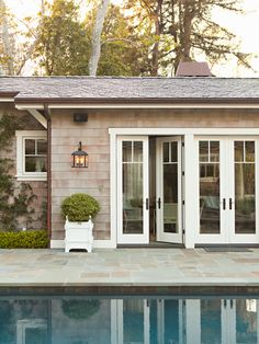 Peaceful - slate pool surround, shake shingles with white trim, white Versailles planter. Two-over-one windows and French doors leave views uninstructed.   Pool-house by Lee Ann Thornton
