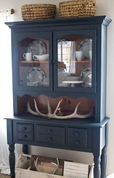 Farmhouse style and painted furniture. Navy blue hutch and white dishes.