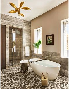 Travertine wall panels and a geometric stone-tile floor lend warm tones to the master bath of a Manhattan penthouse by Dufner Heighes; the vintage light fixture is by Angelo Lelli, the framed collage is by Mark Welsh, the tub is by Wetstyle, and the tub fittings are by Kallista | archdigest.com