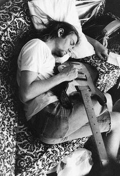 Kurt Cobain sleeps with his guitar.
