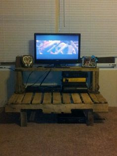 TV stand made from a pallet and old floor wood from a stock trailer