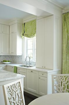 -crown molding on ceiling:how it separates the kitchen from the seating nook for eating -Island w/ nothing on it -cabinets go ALL the way down to hardwood floor-easy for cleaning -Window above kitchen sink