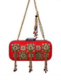 A perfect companion for your evening dress by Meera Mahadevia. Now available on strandofsilk.com! #indianaccessories #indianhandbags #purse #bag #embroidery #beautiful #charming #contemporarystyle #festivelook #glamorous #elegant #indianfashion #meeramahadevia #strandofsilk #chic #red #gold #tasseled