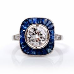 This classic diamond sapphirering is crafted in solid platinum. The Center set with one genuine round diamond, approx. 1.15 ct, G-H colorset in bezel with very nice SI1 clarity. It is surrounded by some 22 Calibrated French cut sapphires, approx.1.07 ct. There is millegrain work all around and accentuating 6 European diamond on the shoulders of approx.0.15 ct, H color, VS clarity. This item is in excellent condition! Weight is approx: 4.1 Grams Width/Height is approx: 13.5mm x 5 mm Rin...