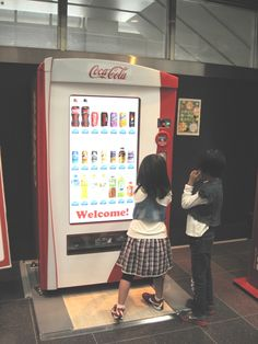 "Kids playing with the Interactive touchscreen Coca-Cola Vending machine in Japan, Tokyo Hanada Airport - ""interactive Happiness Machine"""