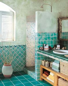 Ocean-themed tile bathroom with open shelving under the sink