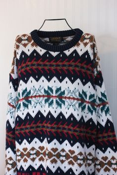 This is a 90s vintage Eddie Bauer sweater for men in size large. It has a cool nordic style to it and is in really great vintage condition. The colors are white with navy blue, burgundy, gold and teal