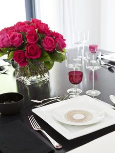 A classic bouquet of roses and colored stemware add interest to everyday dinnerware