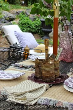 """A sophisticated yet muted European color palette is just the ticket for this al fresco dining table. Incorporate lots of texture for interest. Jute place-mats with chunky cotton tassels, linen napkins and a woven wicker silver ware caddy all give this table a laid back European country vibe. Turn your outdoor living at home into a """"Staycation"""" with a pretty setting for dining like this one.  Sponsored by HomeGoods."""