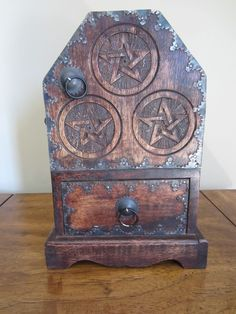 """TRIPLE PENTAGRAM Wooden CHEST Cupboard STASH Box 11"""" Wiccan Pagan Altar Coffin - $39.99. Triple pentagram/pentacle wooden chest. Excellent pre-owned vintage condition. Heavy solid wood with 2 shelves behind a door and a drawer. 11"""" high. Makes a perfect hiding spot for all sorts of treasures you want to stash. PENTAGRAM CHEST and CUPBOARD Triple Pentagram Altar Box Wicca Pagan Celtic Dimensions: 11"""" x 7 5/8"""" x 4 1/2"""" This chest and cupboard piece is a beautiful addition to any altar, providing m Pagan Altar, Wiccan, Witch Alter, Stash Jars, Hiding Spots, Wood Chest, Metal Trim, Pentacle, Coffin"""