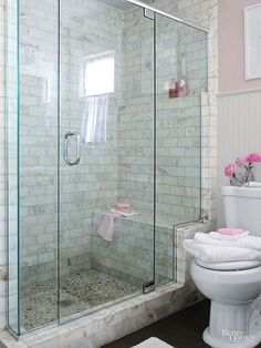 Add a walk-in shower that enhances a small bathroom's usefulness and beauty. This shower stands out in a simply furnished bath, thanks to its distinctively tiled walls and river-rock-tiled floor that are easily seen through a frameless glass shower enclosure. The glass enclosure stair-steps up a marble frame, highlighting the shower bench and a toiletry shelf that aligns with the beaded-board wainscoting's upper trim./