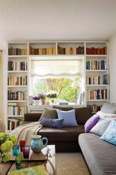 00365416. Salón con sofá con chaise longue en negro y estanterías con libro alrededor de la ventana_00365416