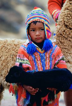 Peruvian boy carries black lamb, Peru, South America - Photo by Tim Graham