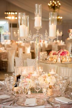 A tall lucite candelabra is surrounded by bud vases and floating votives, creating a mesmerizing effect.