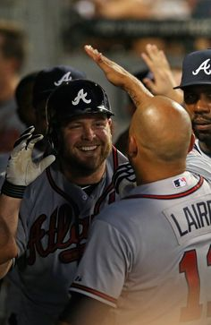 Brian McCann #16 of the Atlanta Braves is greeted by teammates in the dugout after hitting a three-run homer