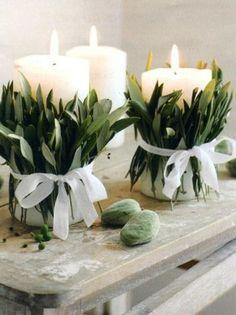 Envuelve velas con ramas de flores o plantas para crear un lindo arreglo de mesa para celebrar a mamá.