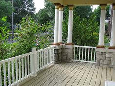 Porch with composite decking, vinyl rails, and stone column bases.